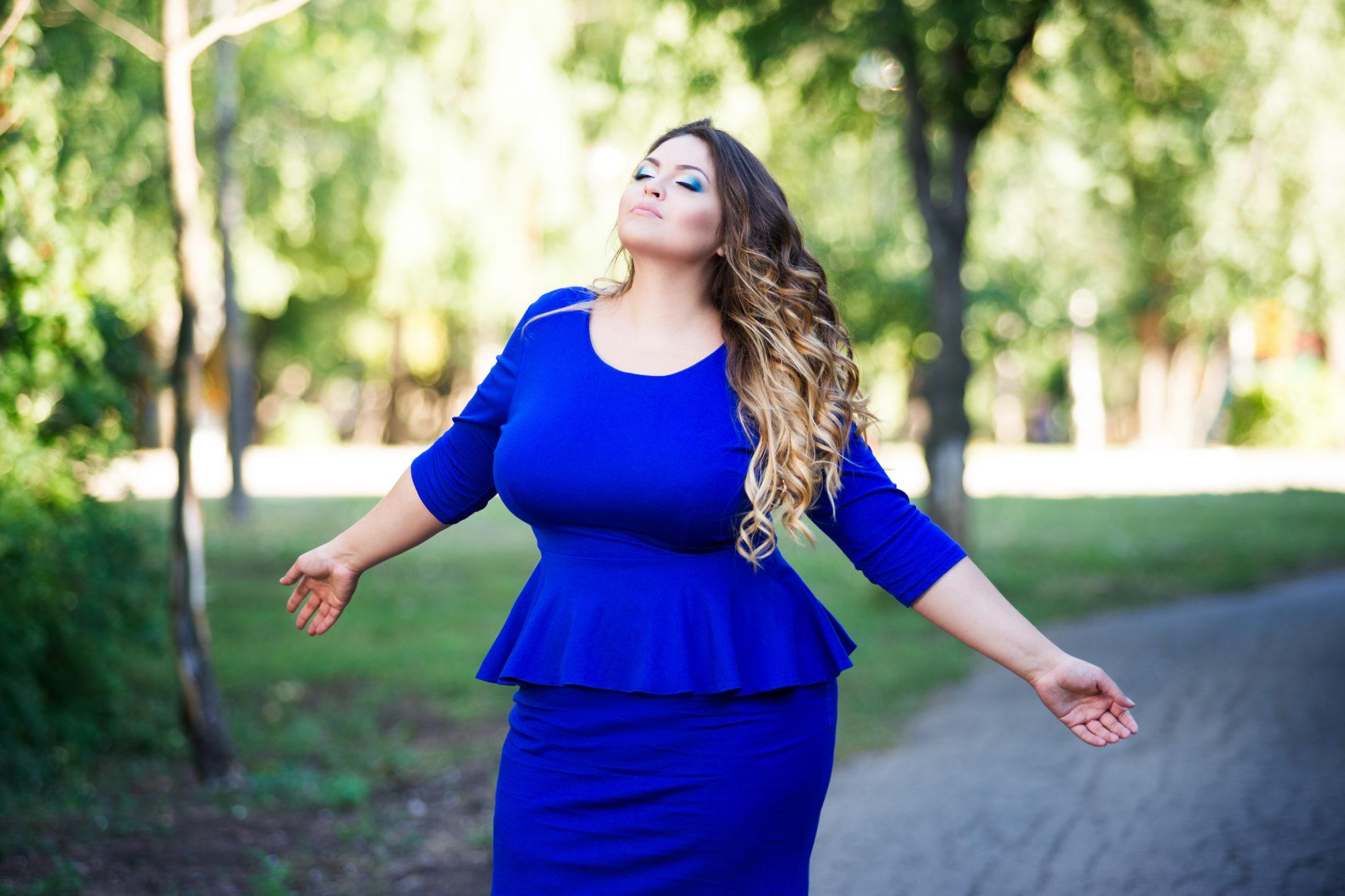 femme ronde en robe bleue éclatante dans un jardin